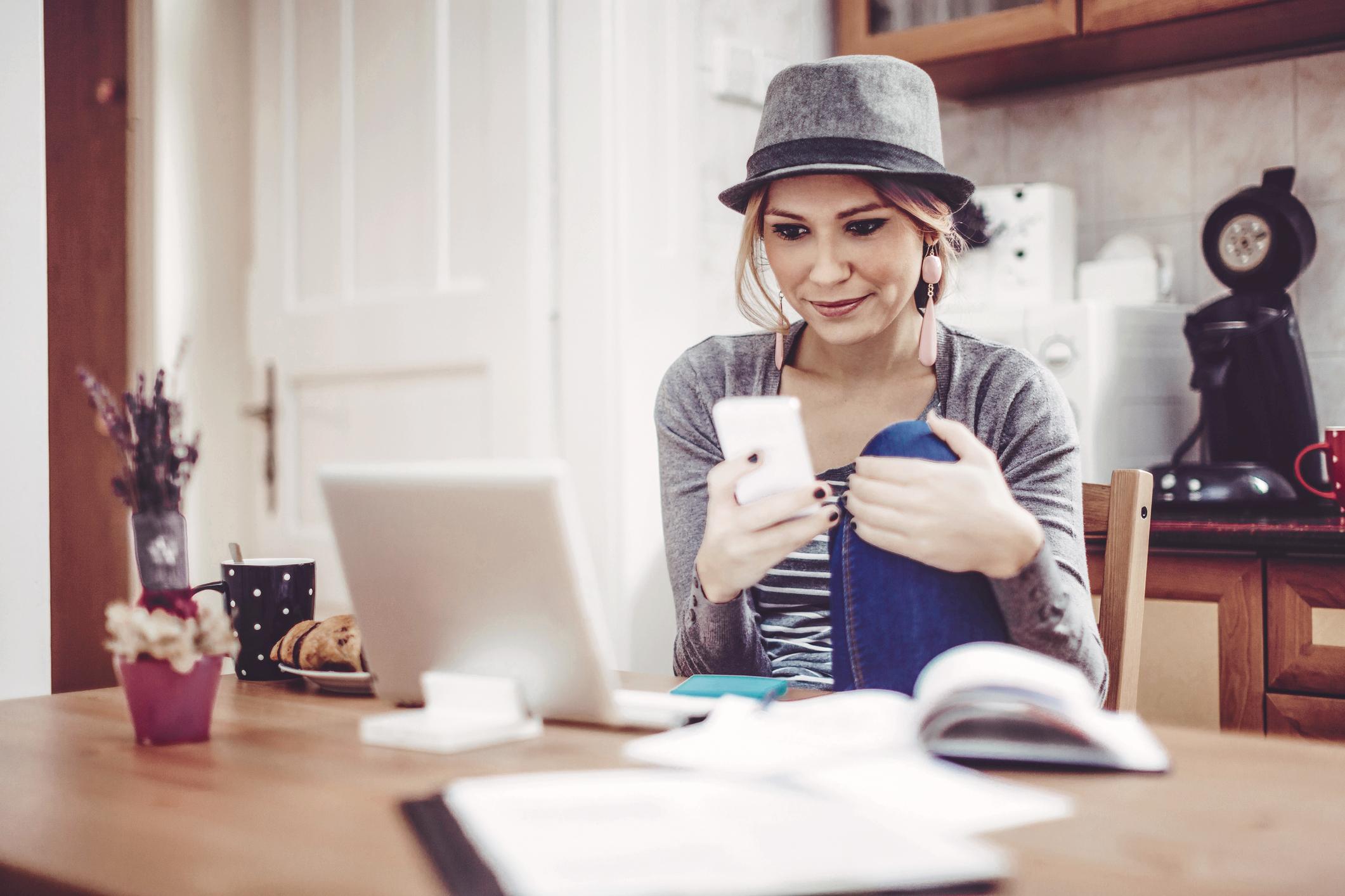 Junge Frau regelt Finanzen mit Handy
