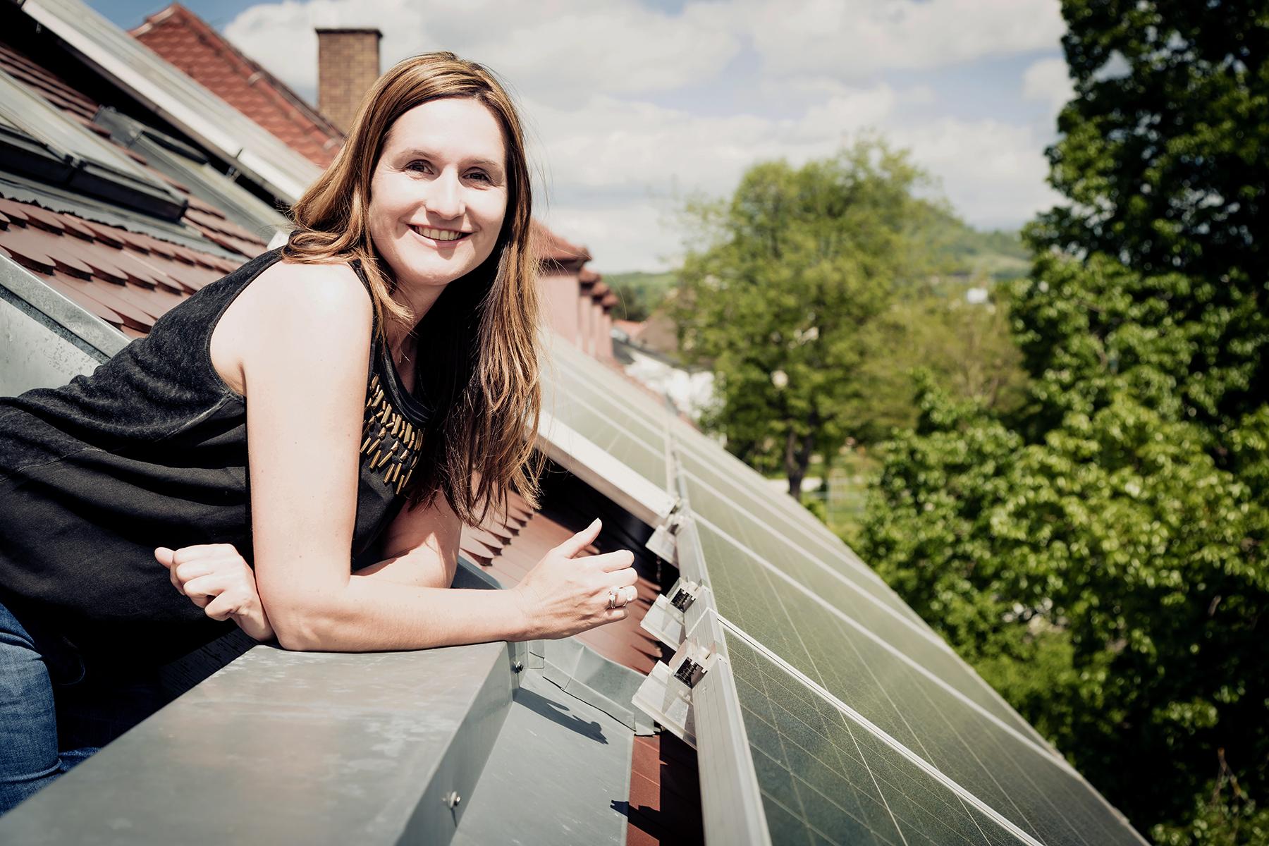 Absicherung Eigenheim: Frau guckt aus Dachfenster